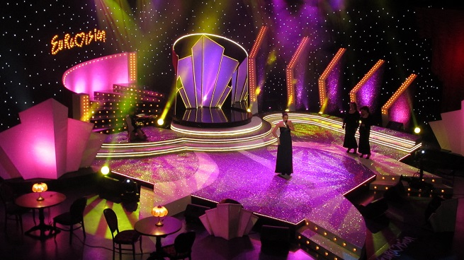 The set of the Bulgarian national Eurovision semi-final dressed in White (GLI009) and gun metal (GLI019) Glittercloth. Plum Velvet Velour (VEL003) curtains were hung around the edges of the set and white Scenic and Artist Canvas (CAN043) used to cover the upright scenery.
